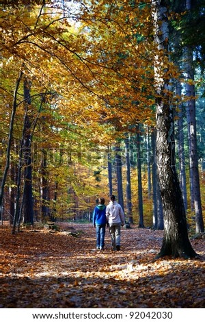A woman and her child for a walk in an autumnal forest.