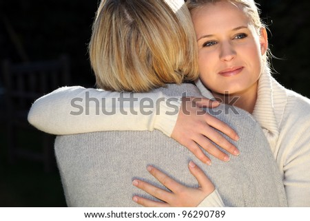 A woman and her daughter hugging. - stock photo
