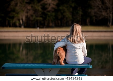 A woman and her dog on a bench by a lake - stock photo