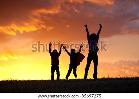 A woman and her two kids jump for joy at sunset.