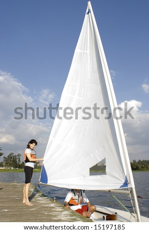 A woman and man are next to a sailboat.  The man is sitting inside the boat.  The woman is standing beside it fixing the sail and smiling at the camera.  Vertically framed shot. - stock photo