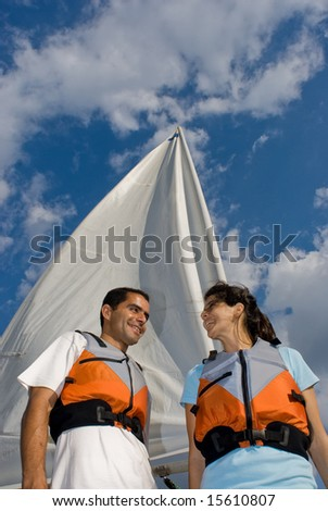 A woman and man are next to a sailboat.  They are smiling and looking at each other.  Vertically framed shot. - stock photo