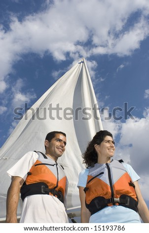 A woman and man are next to a sailboat.  They are smiling and looking away from the camera.  Vertically framed shot. - stock photo