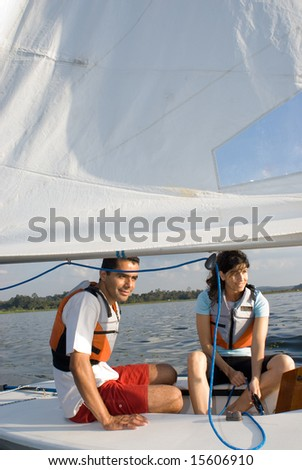 A woman and man are sitting inside a sailboat.  They are smiling and looking away from the camera.  Vertically framed shot. - stock photo