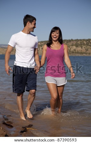 A woman and man holding hands walking in the water smiling and laughing. - stock photo