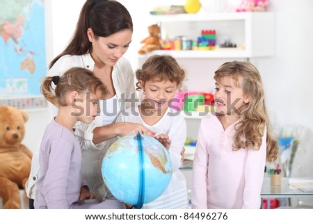 a woman and three little girls watching a globe - stock photo