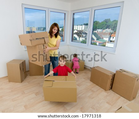 A woman and two children with cardboard boxes in new home. - stock photo