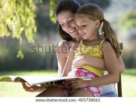 A woman and young girl sitting in the garden reading a book - stock photo