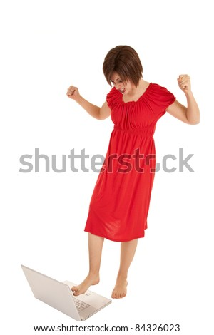 A woman angry at her computer getting ready to stomp on it with her foot. - stock photo