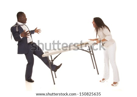 A woman angry with her business partner throwing a table at him. - stock photo