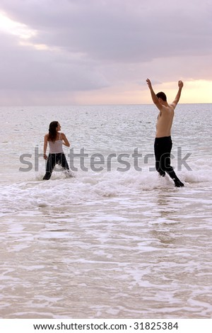 a woman appears to be running into the ocean followed by a tall man, shirtless with his arms up, they are playing in the water at sunset. - stock photo