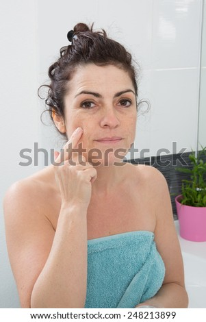 A woman applying cosmetic cream - stock photo