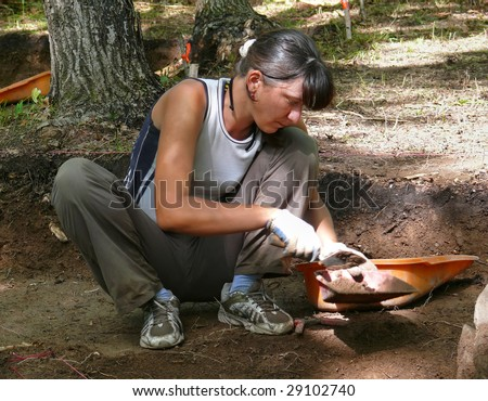 A woman-archaeologist does digging of delubrum of Far East. - stock photo