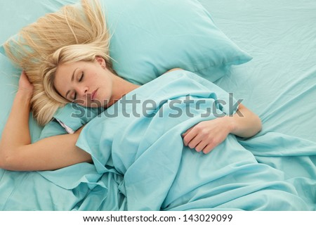 A woman asleep in her bed with the sheets wrapped up around her
