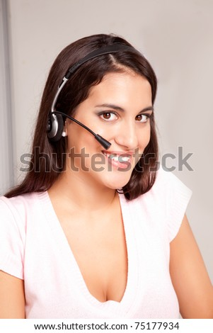 A woman at a call center smiling at the camera - stock photo