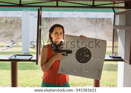 A woman at a shooting range with gun and target - stock photo