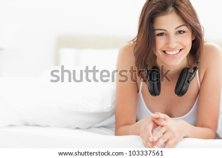 A woman at the end of the bed with headphones around her neck, she is smiling while looking forward. - stock photo