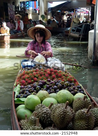 a woman at the floating market in bangkok, thailand - stock photo