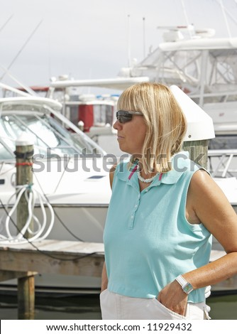 A woman at the marina with boats in the background.