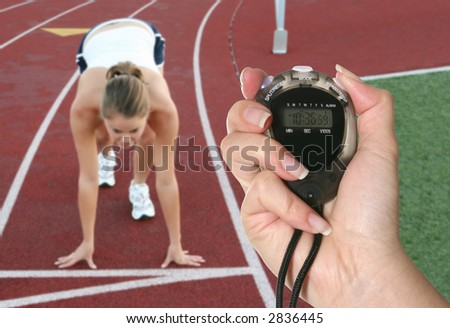 A woman at the starting line ready to race being timed by a stopwatch - stock photo