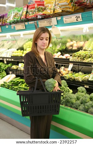A woman at the supermarket shopping for groceries - stock photo