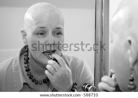 A woman bald due to a health issue, putting on makeup in the mirror. - stock photo