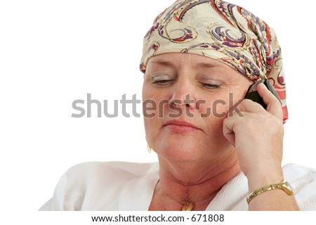 A woman, bald from chemotherapy, having a serious cell phone conversation. - stock photo