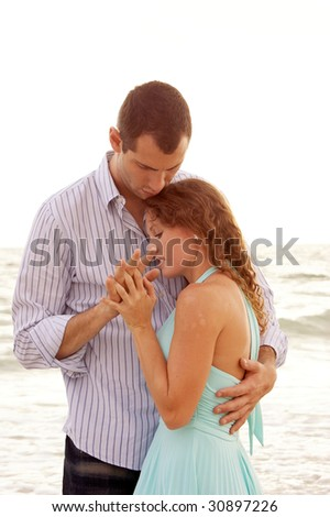 A woman being held close by her man, they are holding hands and they look like they are having a private with ocean waves in the background. - stock photo