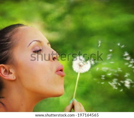 a woman blowing on a dandelion