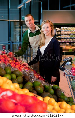A woman buying fruit and vegetables at a supermarket, receiving help from a grocer - stock photo