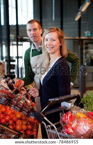 A woman buying fruit at a supermarket receiving help from a store clerk - stock photo