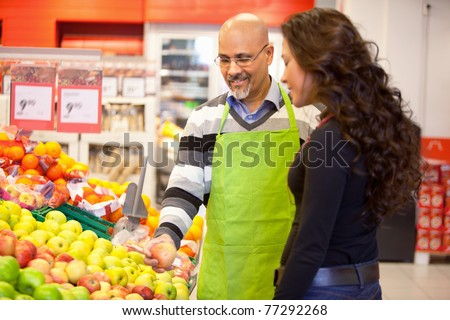 A woman buying groceries receiving help from a store clerk - stock photo