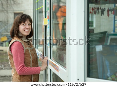 A woman buys something at the newsstand