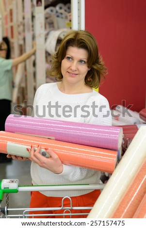 A Woman buys wallpaper in the store - stock photo