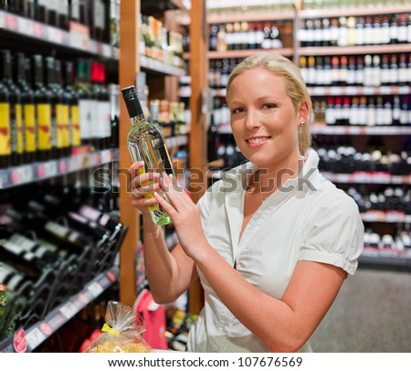 a woman buys wine in a supermarket. wine rack with wines from around the world. - stock photo