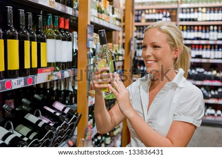 a woman buys wine in a supermarket. wine shelf with wines from around the world. - stock photo