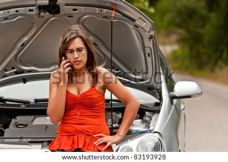 A woman calls for assistance using her mobile phone, after her car broke down on the road side - stock photo
