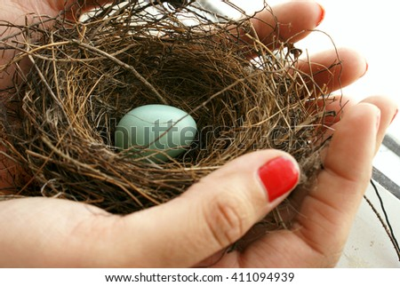 A woman cares for an abandoned nest egg. - stock photo