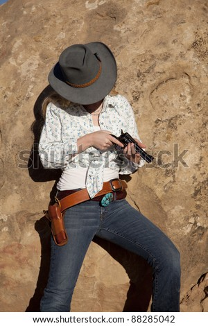 A woman checking her pistol looking down. - stock photo