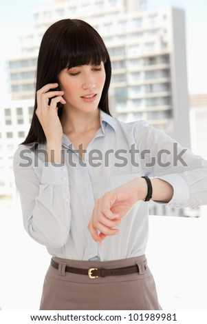 A woman checking the time as she makes a phone call - stock photo