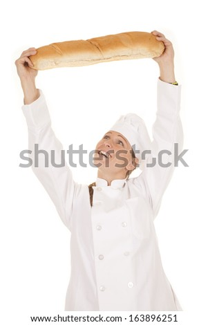 a woman chef so happy with her loaf of bread she is holding it up over her head,