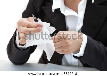 A woman cleaning a pen with a white tissue
