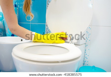A woman cleans a bathroom toilet with a scrub brush. - stock photo