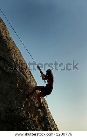 A woman climbs a cliff in California
