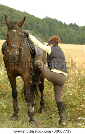 A woman climbs into the saddle. - stock photo