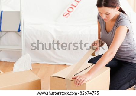 A woman closing a cardboard with tape - stock photo