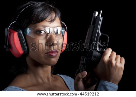 A woman cocks chambers a bullet in a pistol. She's wearing protective shooting gear. Black background. - stock photo