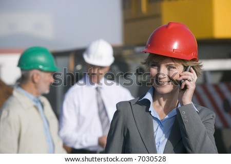 A woman construction engineer on the phone with co-workers behind her
