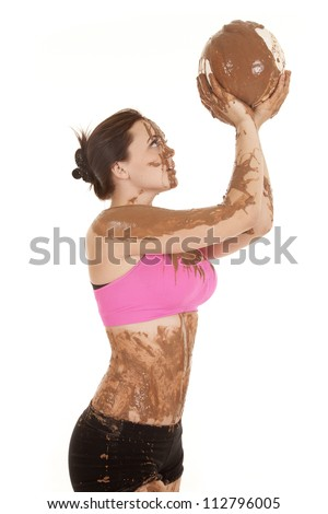 A woman covered in mud with a volleyball covered in mud. - stock photo
