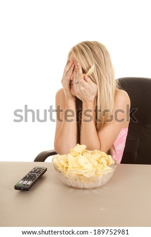 A woman covering her eyes watching t.v. and eating potato chips. - stock photo